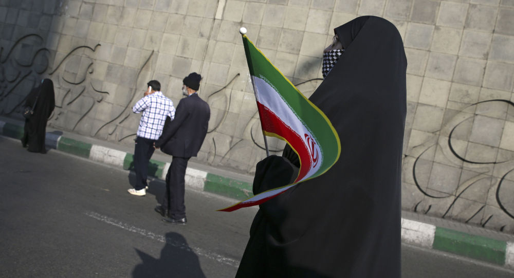 Kobieta z irańską flagą na ulicy Teheranu