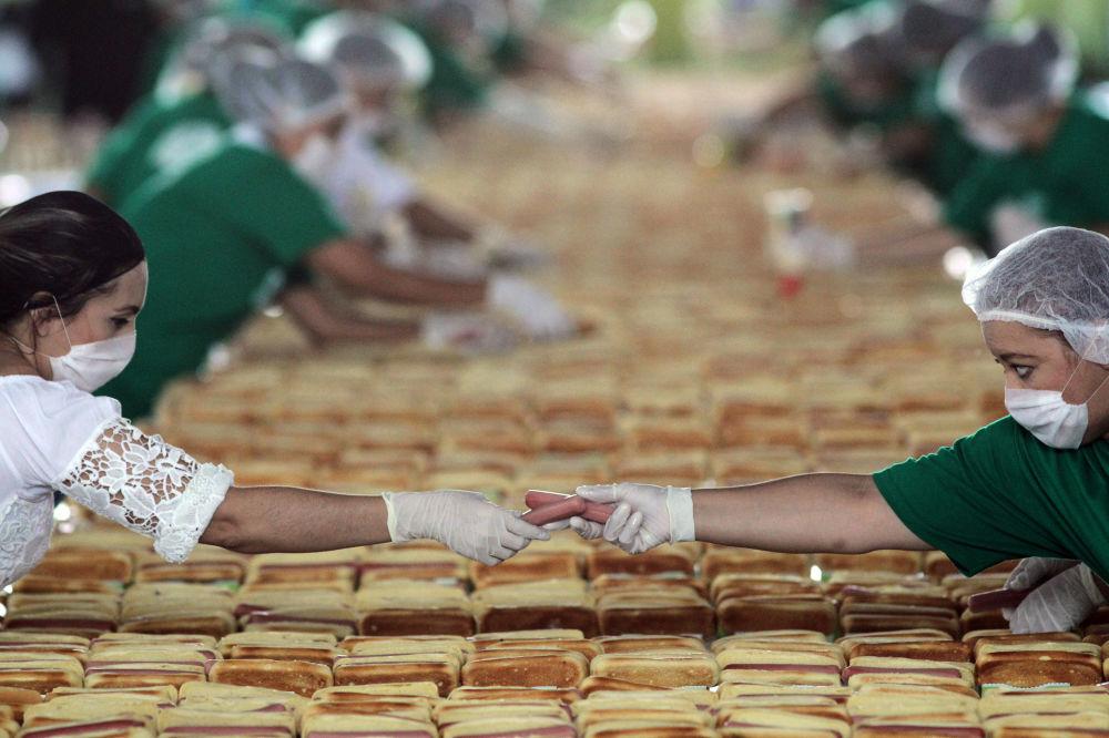 Ludzie przygotowują hot dogi, próbując pobić rekord Guinnessa w najdłuższej linii z hot-dogów w Guadalajara w Meksyku