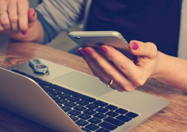 Kobieta z telefonem przed komputerem