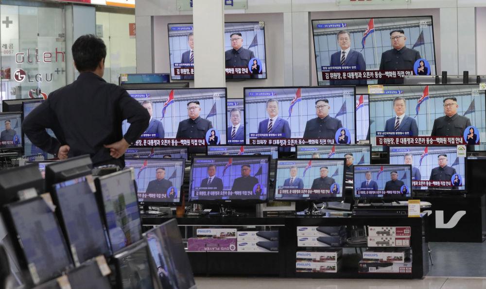Mężczyzna ogląda ceremonię powitania prezydenta Korei Południowej