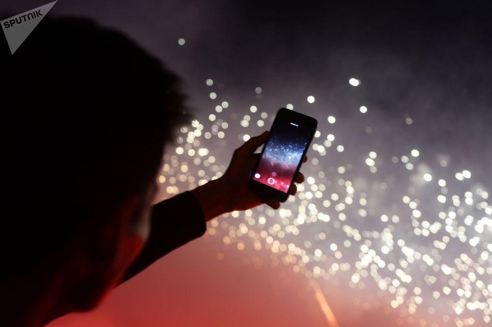 """Jeden z widzów fotografuje sztuczne ognie podczas ceremonii otwarcia międzynarodowego festiwalu """"Krąg światła"""" w rosyjskiej stolicy"""