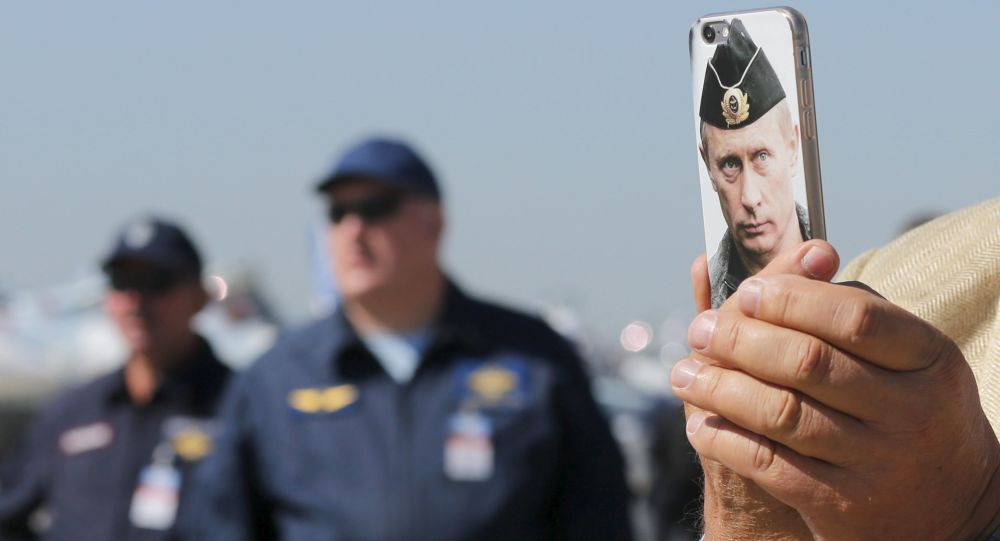 Gość Międzynarodowego salonu lotniczego i kosmicznego MAKS - 2015 robi zdjęcia komórką z obrazkiem prezydenta Rosji Władimira Putina