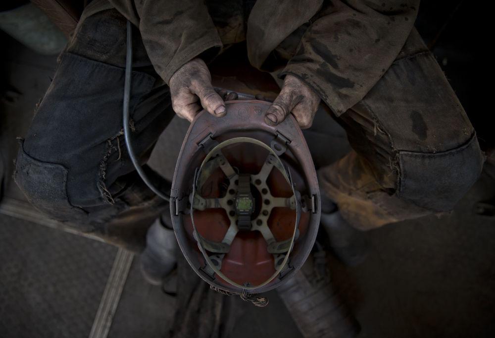 Górnik trzyma kask w jednej z kopalń Doniecka