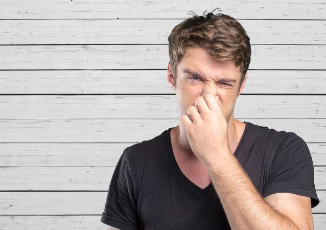Mężczyzna trzymający się za nos