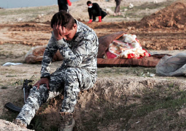 Iracki policjant na miejscu pochówku zbiorowego w rejonie, który znajdował się pod kontrolą PI