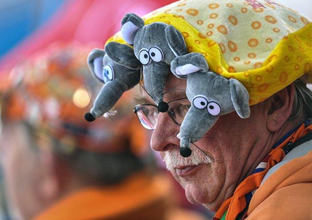 Kibic w śmiesznej czapce z myszkami i serem