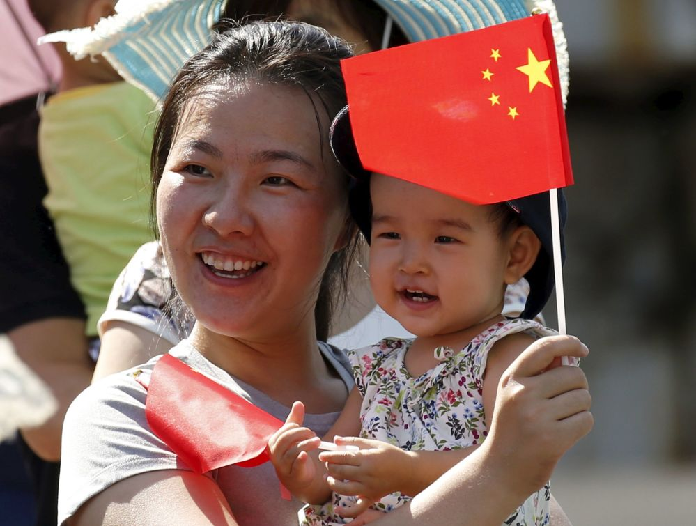 Kobieta z dzieckiem czeka na rozpoczęcie defilady z okazji 70. rocznicy zwycięstwa w II wojnie światowej w Pekinie