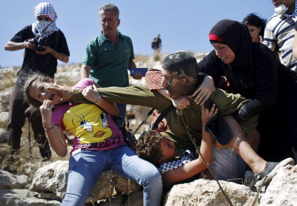 Palestyńczycy biją się z izraelskim żołnierzem podczas akcji protestacyjnej przeciwko osiedlom żydowskim pod Ramallah