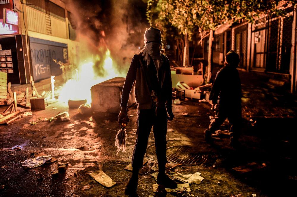 Protestant trzyma butelkę zapalającą podczas starcia z policją w Stambulu