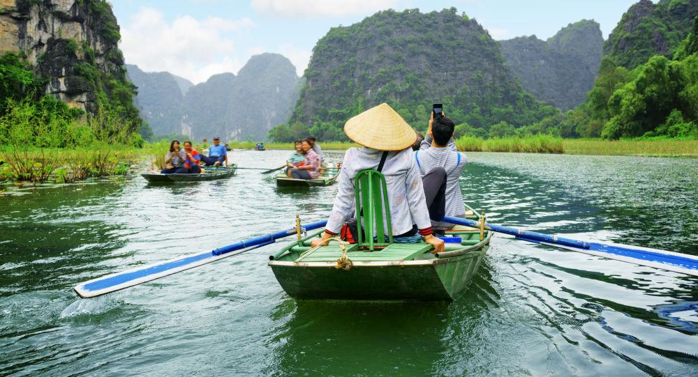 Turyści w łodziach w czasie wycieczki po rzece Ngo Dong we Wietnamie