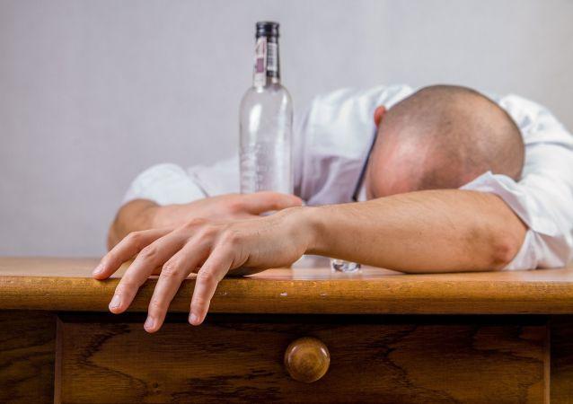Pijany mężczyzna z butelką przy stole
