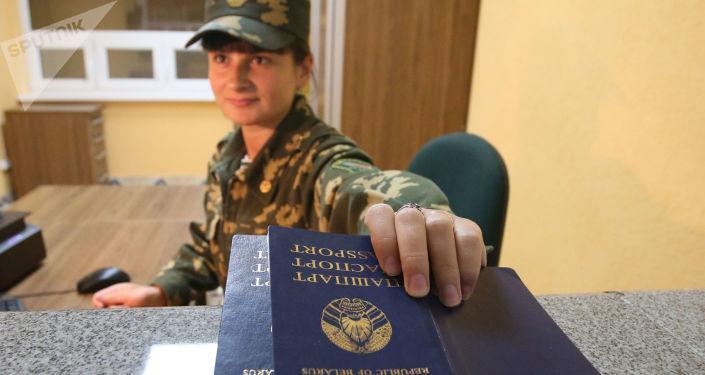 """Strażnik graniczny sprawdza paszporty na przejściu granicznym między Białorusią a Polską """"Pererow"""""""