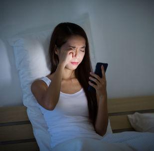 Dziewczyna z telefonem komórkowym w ręce w łóżku