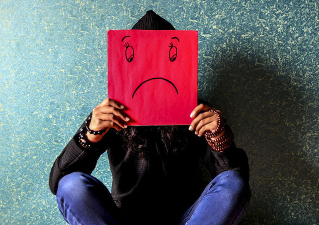 Dziewczyna trzyma kartkę ze smutną buźką
