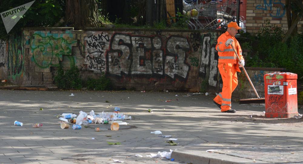 Pracownik służby miejskiej w Hamburgu zamiata śmiecie po akcji protestu