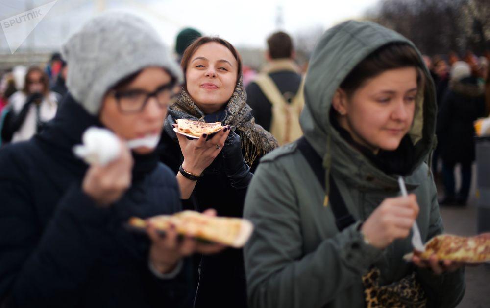 Dziewczyny jedzą bliny podczas świętowania Maslenicy w Moskwie